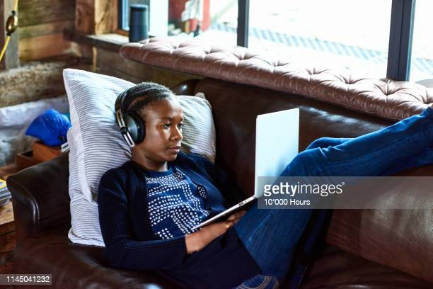 young woman sitting on sofa using laptop with feet up - podcasting stock pictures, royalty-free photos & images