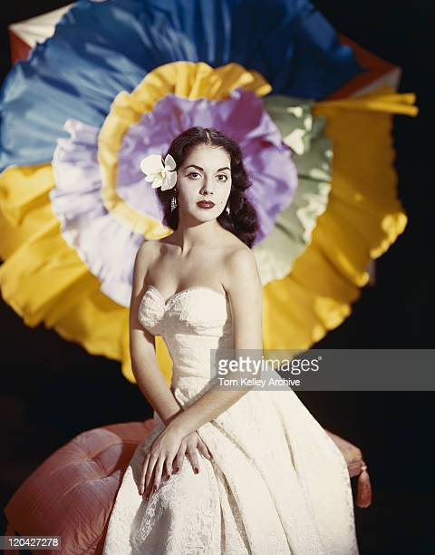 young woman sitting on sofa wearing flower, portrait - 1955 stock pictures, royalty-free photos & images