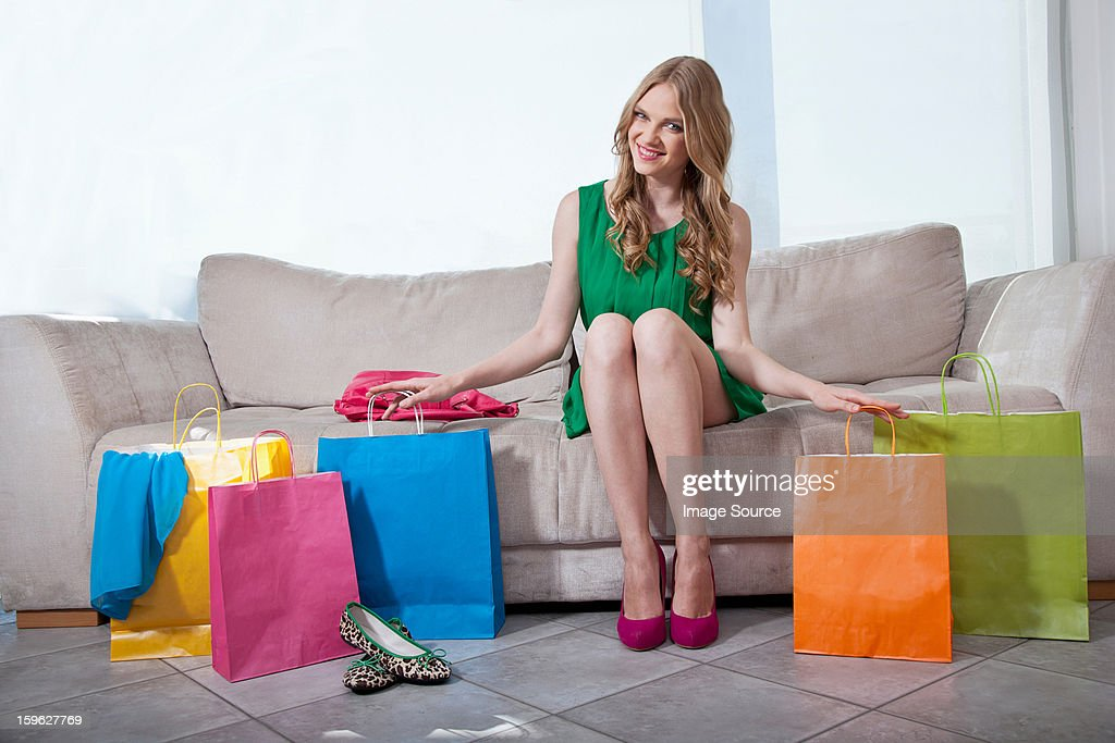 Young woman sitting on sofa with shopping bags : Stockfoto