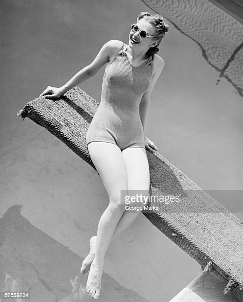 Young woman sitting on springboard, (B&W)