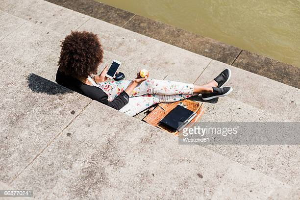 Young woman sitting on stairs eating an apple while looking at her smartphone