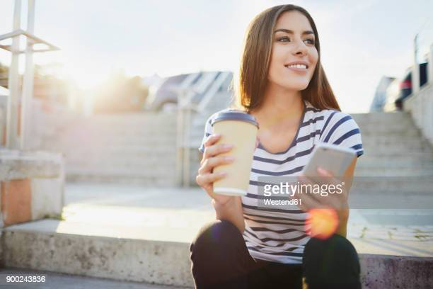 young woman sitting on stairs in the city with phone and coffee - 18 19 jahre stock-fotos und bilder