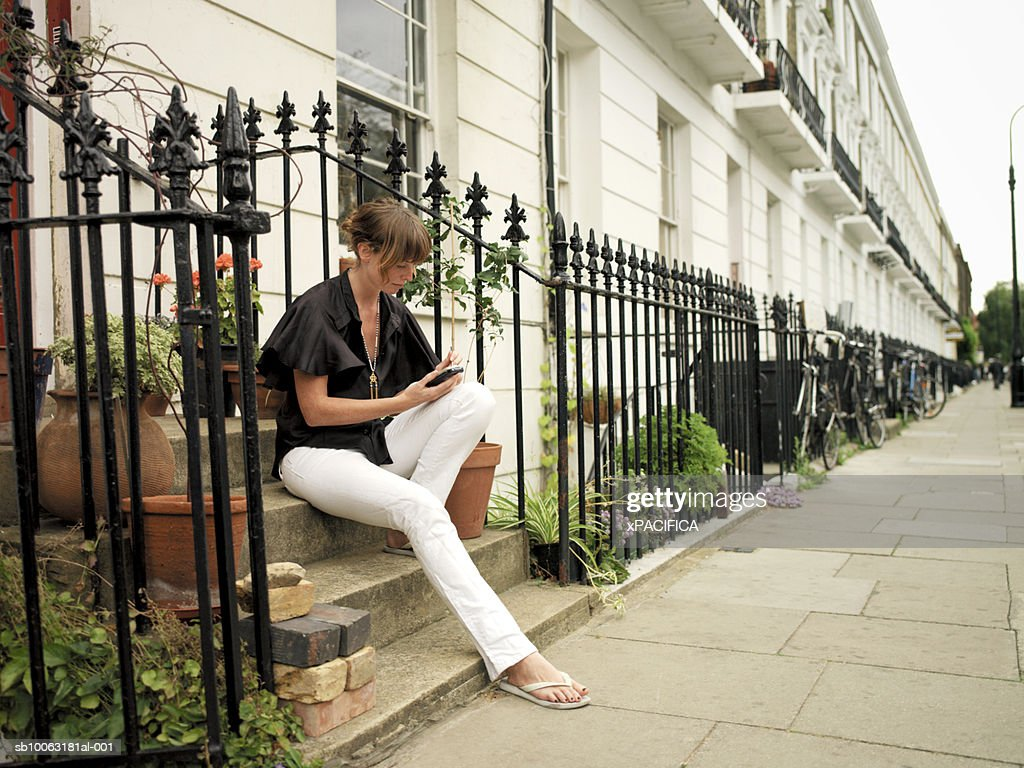 Young Woman Sitting On Stairs Outside House Using Mobile Phone Stock