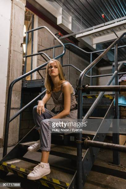 Young Woman Sitting On Steps In Factory