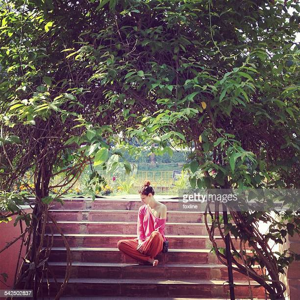 Young woman sitting on steps in garden, India