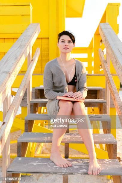 young woman sitting on steps of a lifeguard hut - cabine de plage photos et images de collection