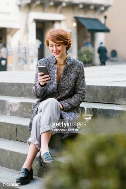 young woman sitting on steps, using smartphone, glass of wine beside her - muro stock photos and pictures