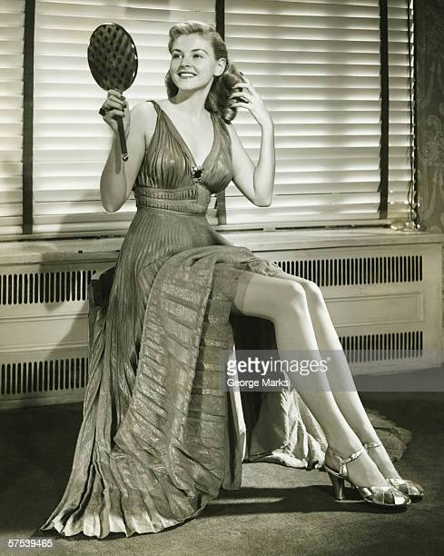 young woman sitting on stool, holding mirror indoors, (b&w) - vintage stockings stock photos and pictures