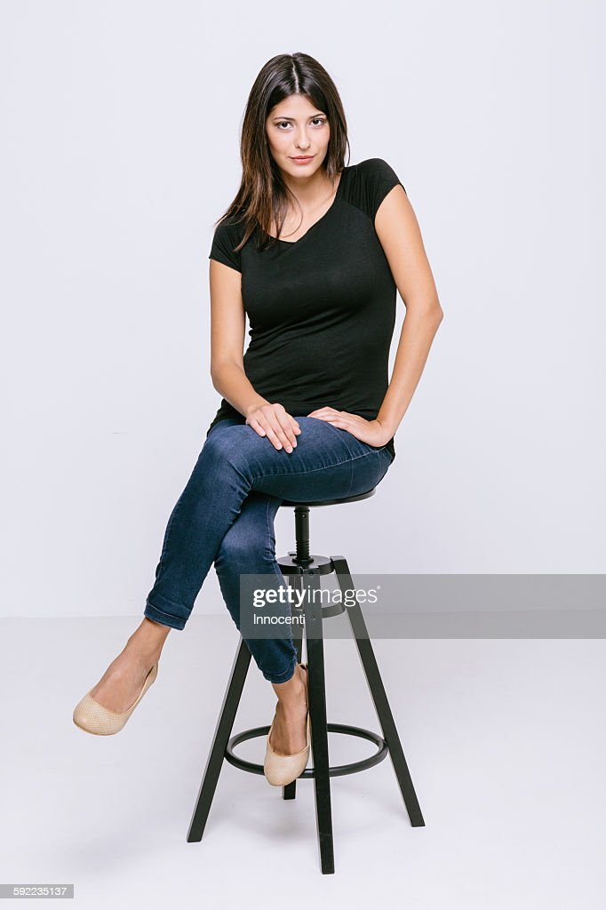 Young woman sitting on stool looking at camera pouting : Stock Photo