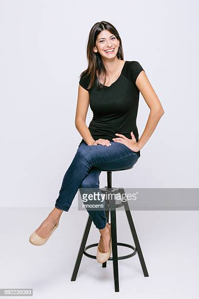 young woman sitting on stool looking at camera smiling - sitting foto e immagini stock