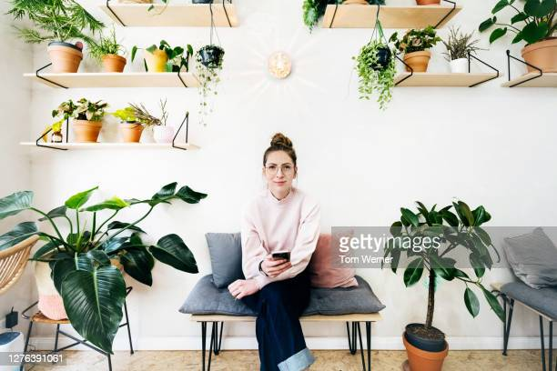 young woman sitting on stool surrounded by plants in café - 30 34 years stock pictures, royalty-free photos & images