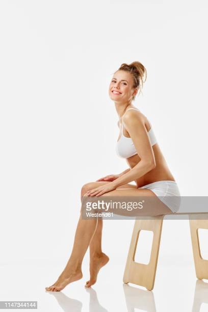 young woman sitting on stool, white background - dessous stock-fotos und bilder