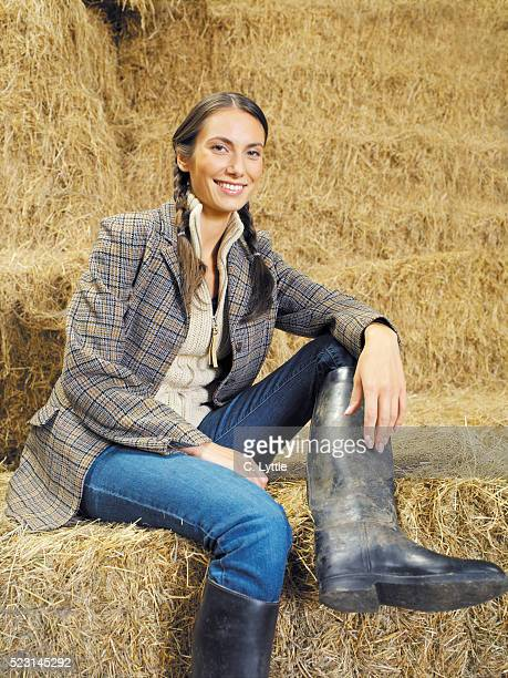 Young Woman Sitting on Straw Bale