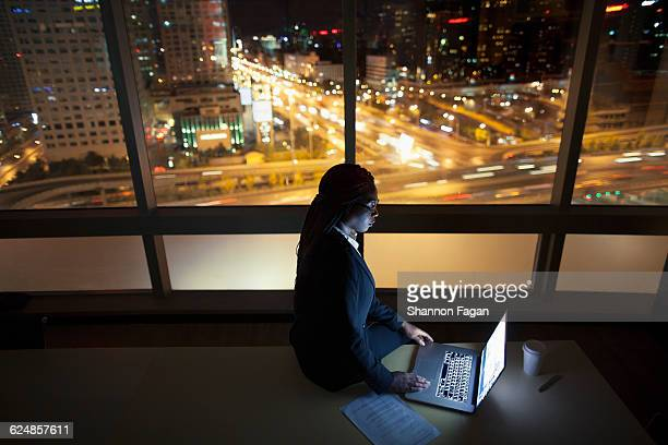 Young woman sitting on table and viewing laptop