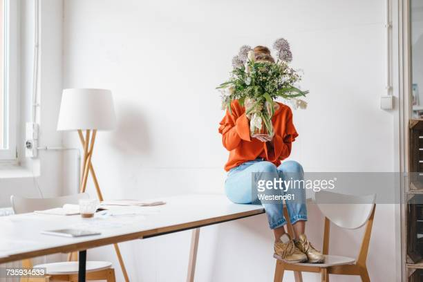 young woman sitting on table holding flower vase in front of her face - verlegen stockfoto's en -beelden