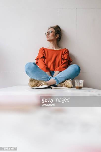 Young woman sitting on table thinking