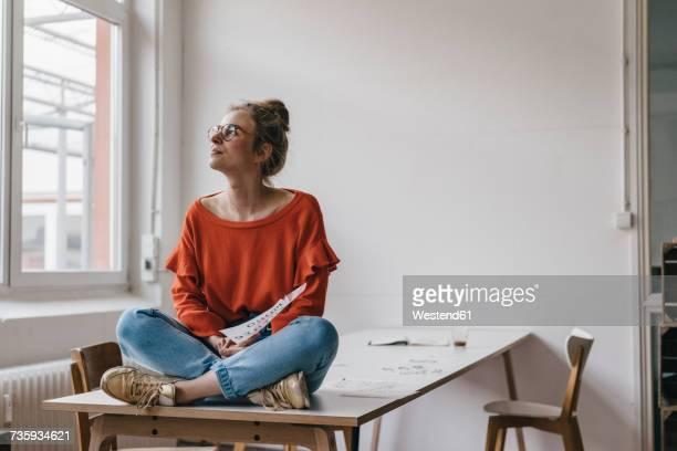 young woman sitting on table thinking - kreativer beruf stock-fotos und bilder
