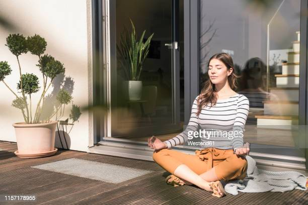 young woman sitting on terrace at home practicing yoga - mindfulness stock pictures, royalty-free photos & images