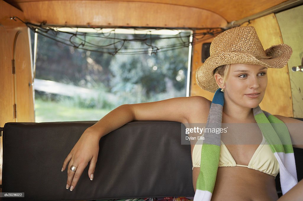 Young Woman Sitting on the Back Seat of a Motor Home Wearing a Scarf and a Straw Hat : Stock Photo