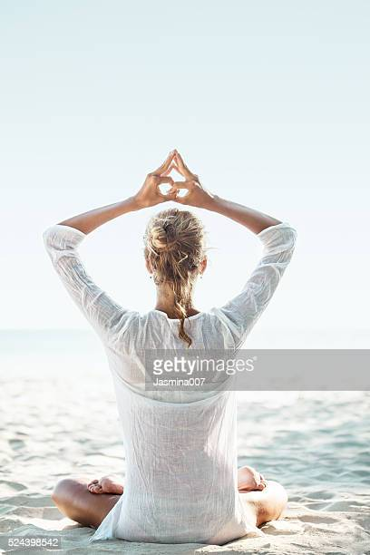 young woman sitting on the  beach and meditating - boeddhisme stockfoto's en -beelden