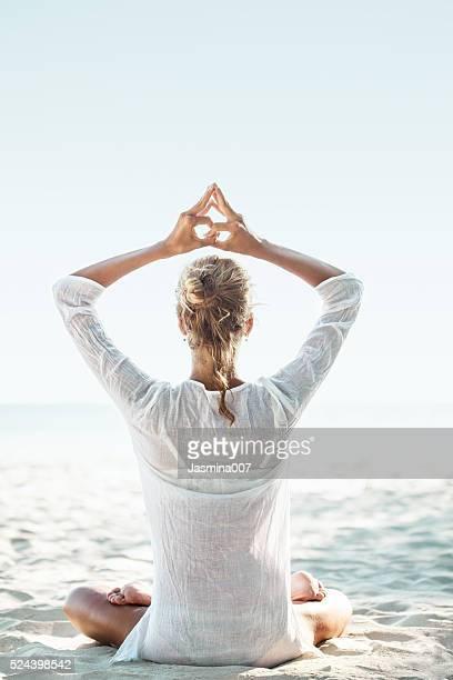young woman sitting on the  beach and meditating - buddhism bildbanksfoton och bilder