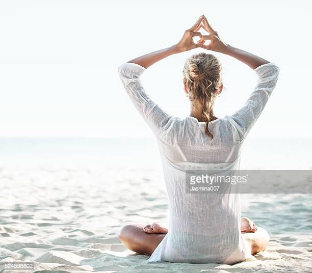 Jeune femme assise sur la plage et de méditation
