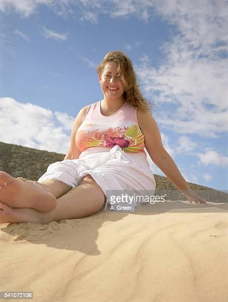 young woman sitting on the beach - dicke frauen am strand stock-fotos und bilder