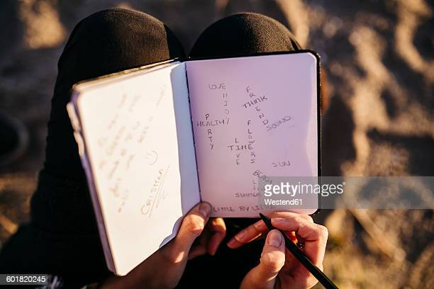 Young woman sitting on the beach using notebook, close-up