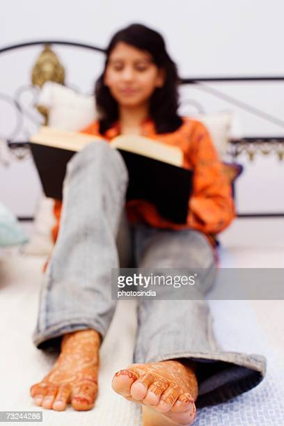young woman sitting on the bed and holding a book - indian female feet stock pictures, royalty-free photos & images