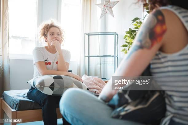 ベッドに座って、彼女の友人に耳を傾ける若い女性 - オルタナティブカルチャー ストックフォトと画像