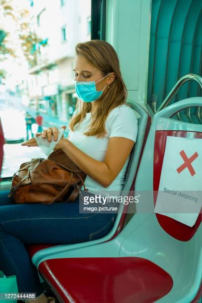 young woman sitting on the bus keeping social distance, wearing surgical mask and desinfecting her hands - antiseptic wipe stock pictures, royalty-free photos & images