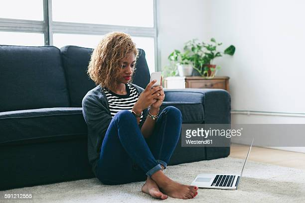 Young woman sitting on the carpet of living room looking at her smartphone