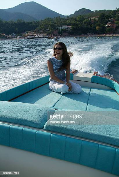 Young woman sitting on the deck of a Riva Motorboat, full throttle, Théoule-sur-Mer, France, Europe