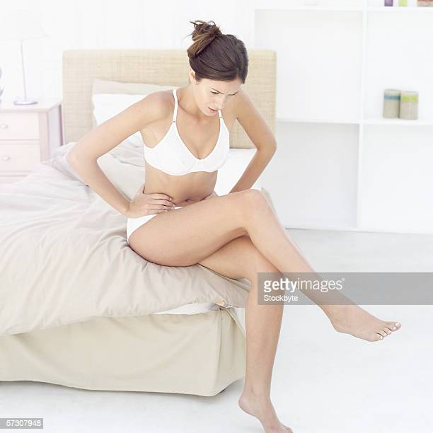 Young woman sitting on the edge of a bed holding her stomach