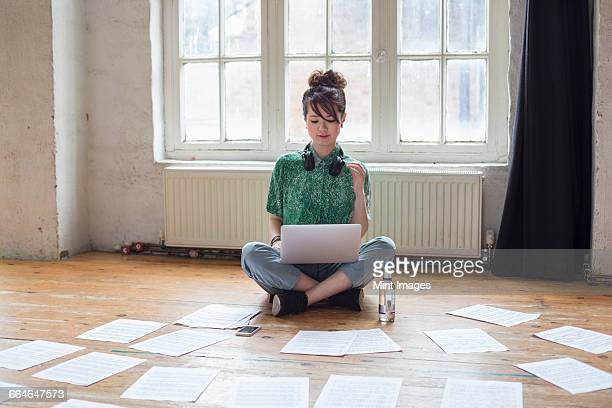 Young woman sitting on the floor in a rehearsal studio, using a laptop computer, looking at sheet music.