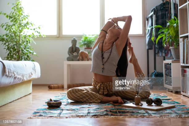 young woman sitting on the floor in asana pose and relaxing while the incense stick burning next to her - incense stock pictures, royalty-free photos & images