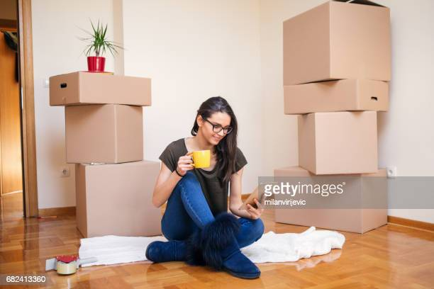 Young woman sitting on the floor in empty apartment