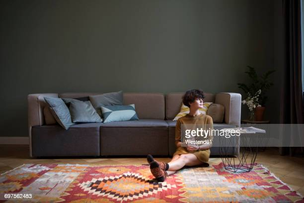 young woman sitting on the floor in her living room looking through window - carpet decor stock photos and pictures