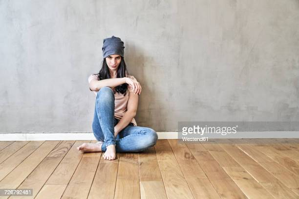 Young woman sitting on the floor in sparse room