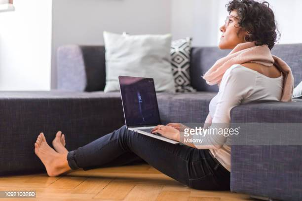 young woman sitting on the floor in the living room working on her laptop. - candid forum stock-fotos und bilder