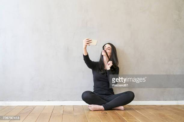 Young woman sitting on the floor taking a selfie