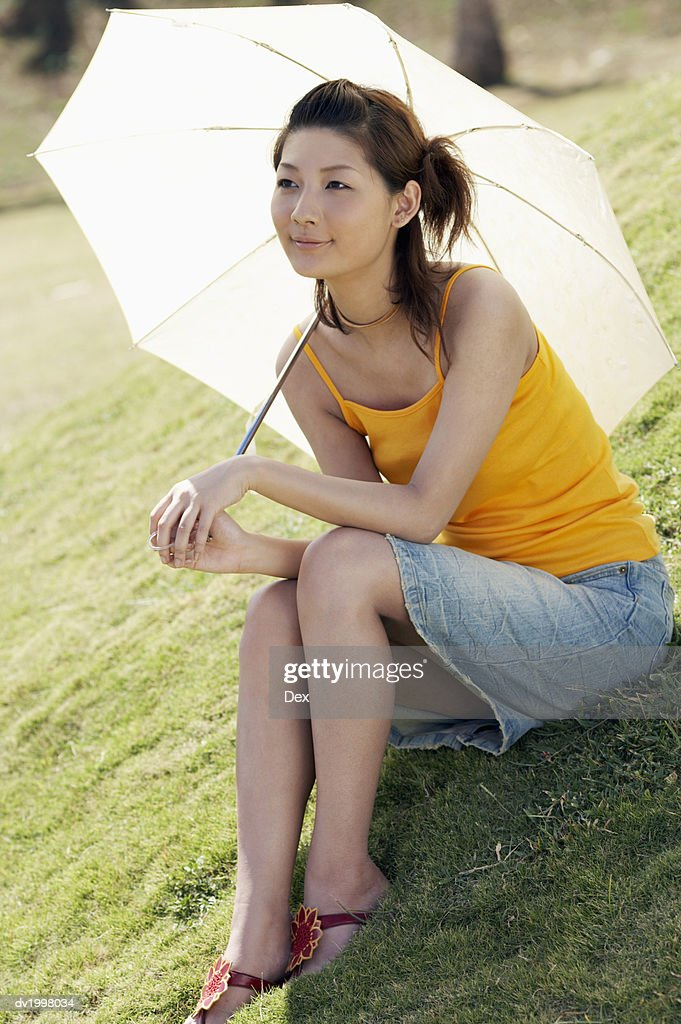 Young Woman Sitting on the Grass and Holding a Parasol : Stock Photo