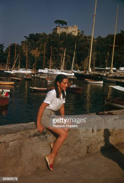 A young woman sitting on the harbour wall at Portofino on Italy's Ligurian coast 1st December 1951 Original publication Picture Post 5599 Portofino...