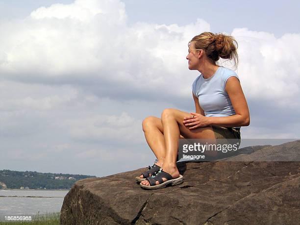 Junge Frau sitzt auf dem rock