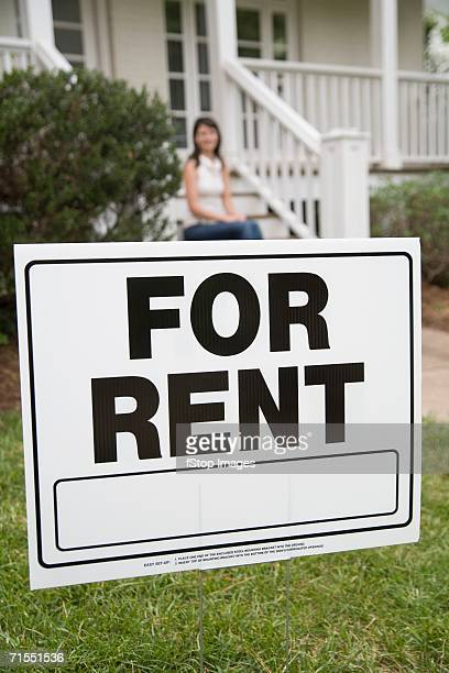 A young woman sitting on the steps of a house behind a ?for rent? sign
