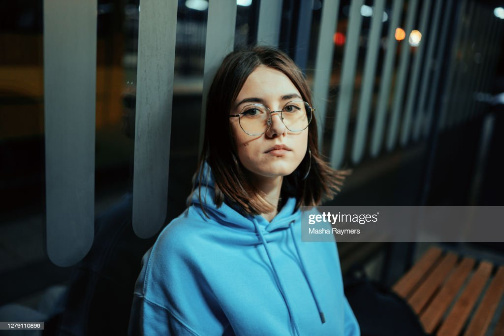 Young woman sitting on the stop at night : Stock Photo