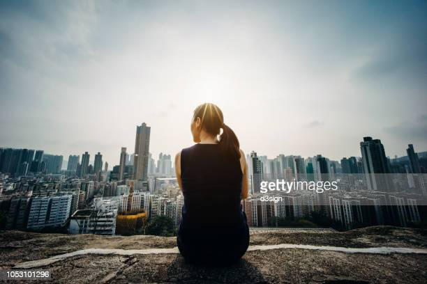 young woman sitting on the top of mountain enjoying the panoramic view of spectacular city skyline - panorama stock-fotos und bilder