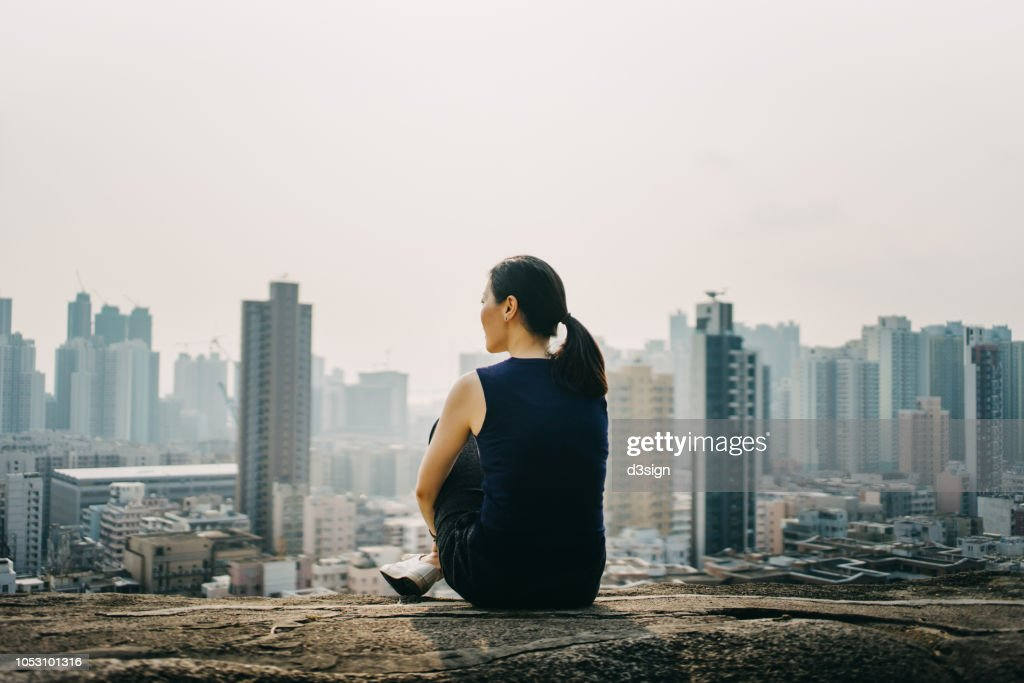 Young woman sitting on the top of mountain enjoying the panoramic view of spectacular city skyline : 圖庫照片