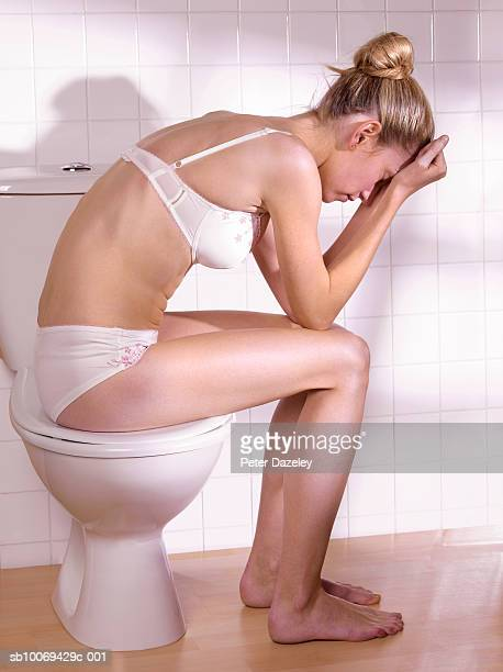 Young woman sitting on toilet lid