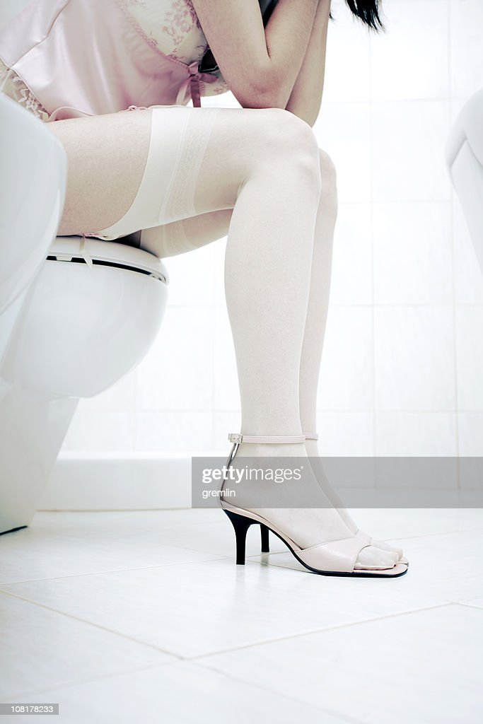 Young Woman Sitting On Toilet Resting Head In Hands Stock